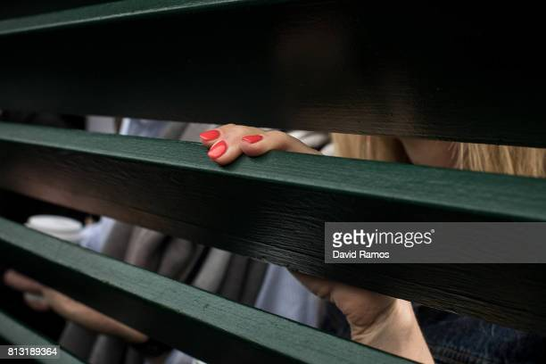 Spectators sneak a look through the fence of court 18 on day nine of the Wimbledon Lawn Tennis Championships at the All England Lawn Tennis and...