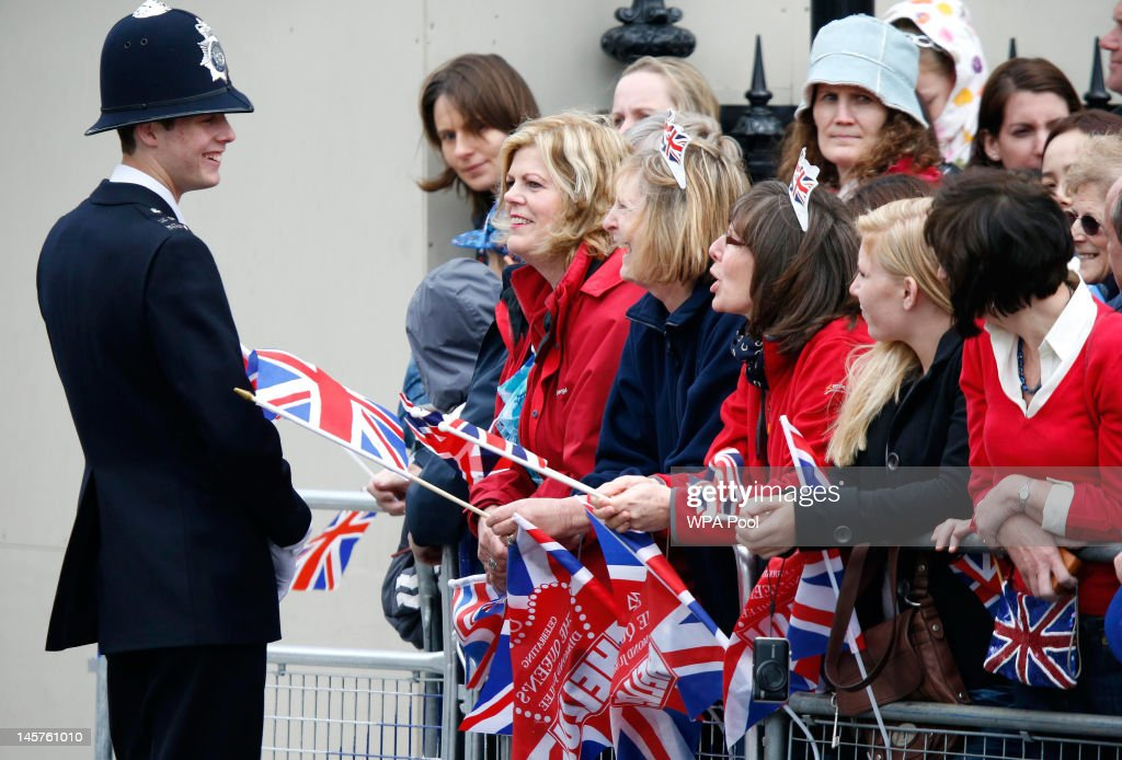 Spectators speak to a policeman as they line Parliament Square during the Diamond Jubilee celebrations on June 5, 2012 in London, England. For only the second time in its history the UK celebrates the Diamond Jubilee of a monarch. Her Majesty Queen Elizabeth II celebrates the 60th anniversary of her ascension to the throne today with a carriage procession and a service of thanksgiving at St Paul's Cathedral.