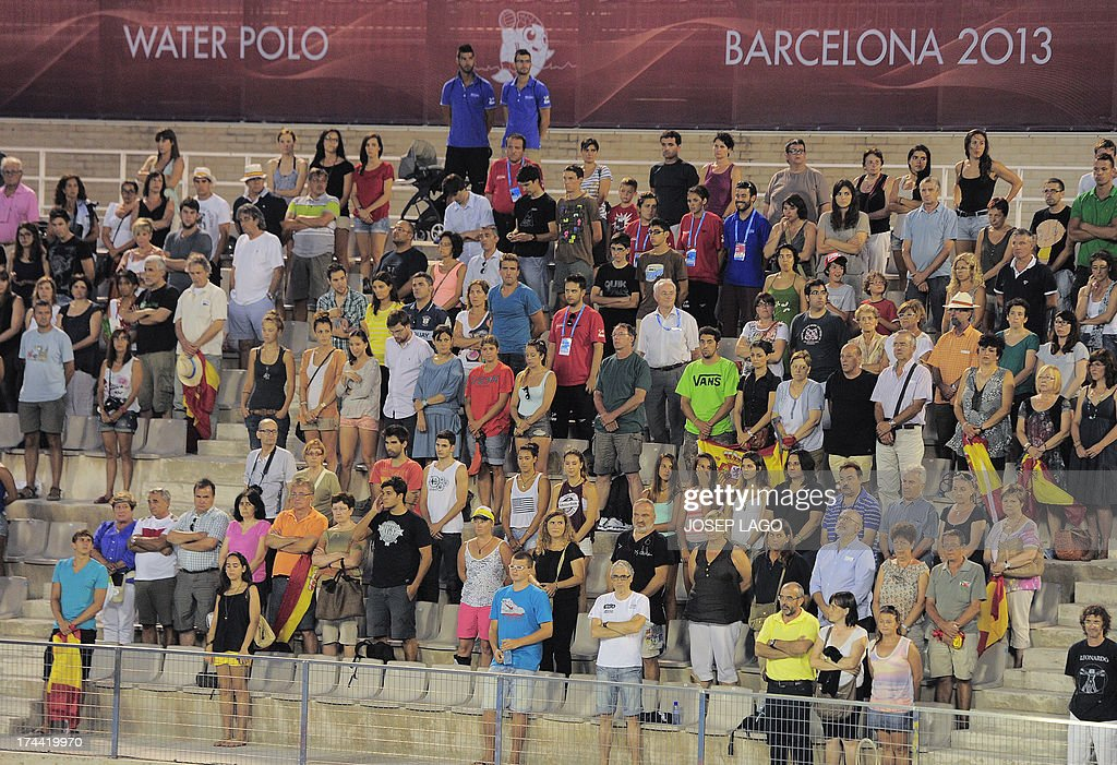 Spectators stand as they hold a minute of silence to pay tribute to the victims who died in a train accident prior to the start of the women's preliminary round of the water polo competition in the FINA World Championships in Barcelona, on July 25, 2013. Spanish police are to grill Thursday the driver of a train that hurtled off the rails at high speed, killing at least 80 passengers in the nation's worst such disaster in decades. The train, travelling from Madrid to the port town of Ferrol flew off the tracks and flipped on to its side, with carriages slamming into each other as it approached the pilgrimage centre of Santiago de Compostela.