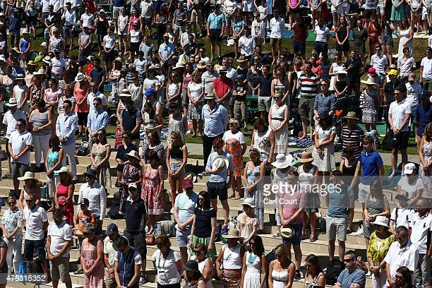 Spectators stand for a minutes silence to pay tribute to the victims of last week's Tunisia beach attack on Murray Mound during Wimbledon Lawn Tennis...