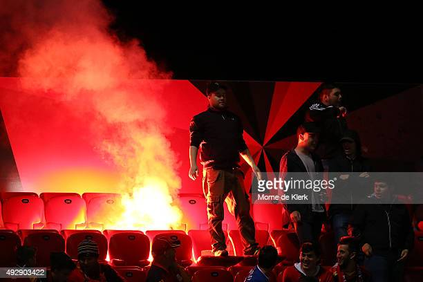 Spectators stand next to a flare during the round two ALeague match between Adelaide United and the Western Sydney Wanderers at Coopers Stadium on...