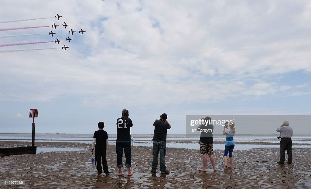 Spectators stand on wet sand on the beach and watch as the RAF Red Arrows perform during the Armed Forces Day National Event on June 25, 2016 in Cleethorpes, England. Armed Forces Day is an annual event that gives an opportunity for the country to show its support for the men and women in the British Armed Forces. The visit by Prime Minister David Cameron to the event came the day after the country voted to leave the European Union.