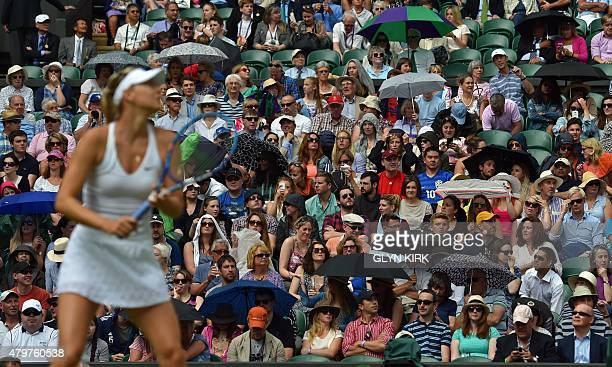 Spectators start to shelter themsleves from the rain as Russia's Maria Sharapova warms up ahead of her women's quarterfinal match against US player...