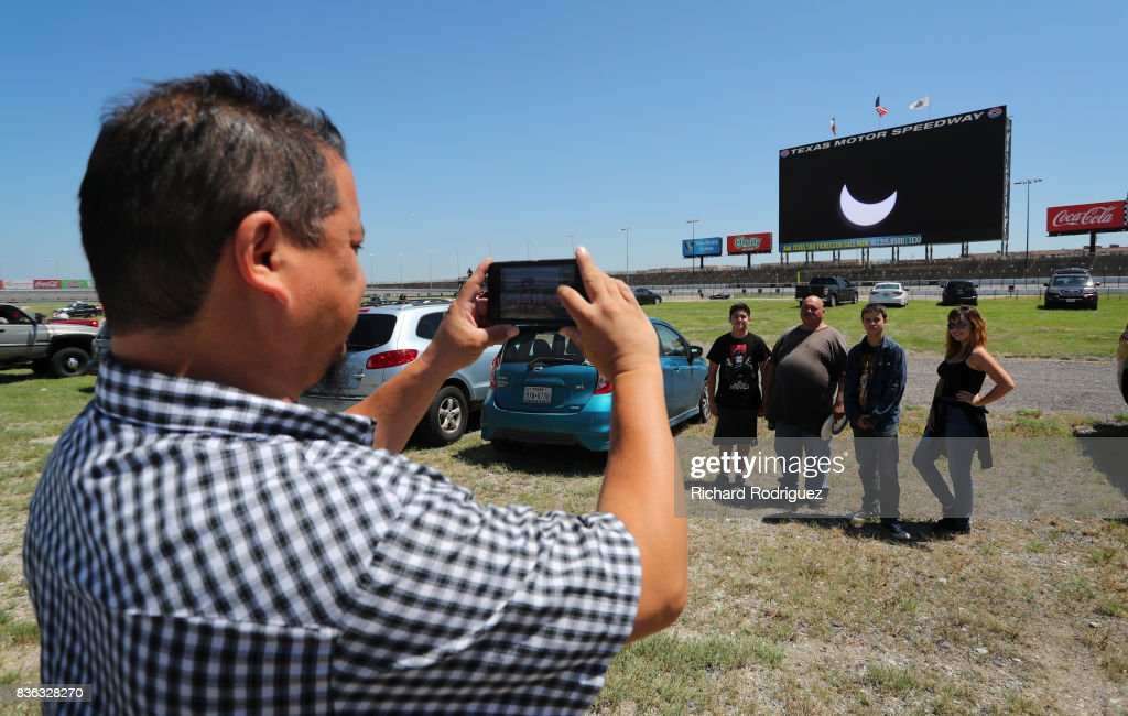 Spectators take a photo with the solar eclipse broadcast on Big Hoss at Texas Motor Speedway on August 21, 2017 in Fort Worth, Texas. Millions of people have flocked to areas of the U.S. that are in the 'path of totality' in order to experience a total solar eclipse. During the event, the moon will pass in between the sun and the Earth, appearing to block the sun. Fort Worth residents will see about 75 percent of the sun blocked by the moon.