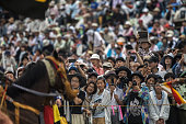 Spectators take photographs of competing samurai horseman in the Kachu Keiba race during the Soma Nomaoi festival at Hibarigahara field in Minamisoma...