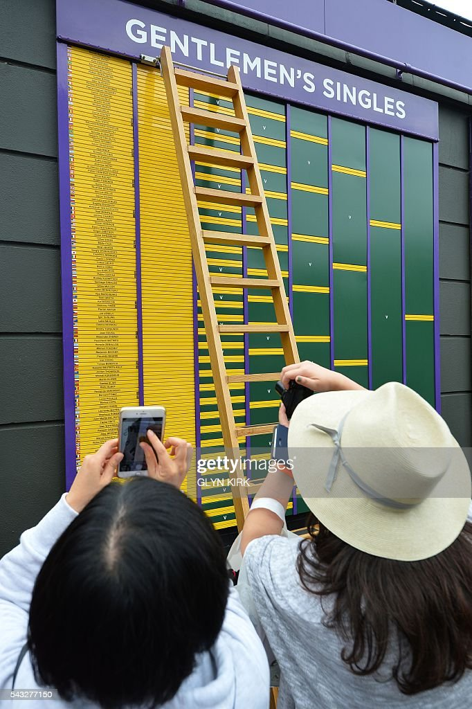 Spectators take photographs of the display of the men's singles draw displayed at The All England Lawn Tennis Club in Wimbledon, southwest London, on June 27, 2016 on the first day of the 2016 Wimbledon Championships. / AFP / GLYN