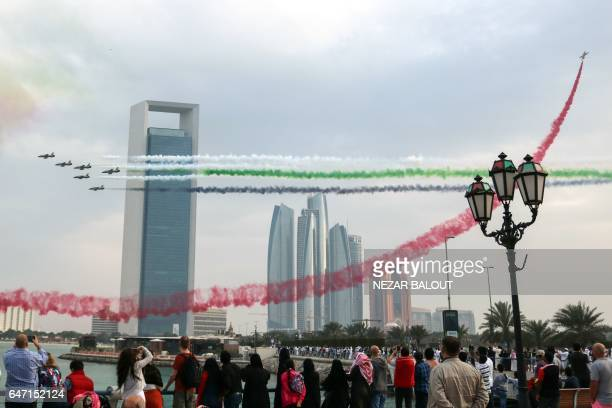 TOPSHOT Spectators take pictures of Emirati planes performing in an airshow as part of the 'Union Fortress Live Military Demonstration' at the Abu...