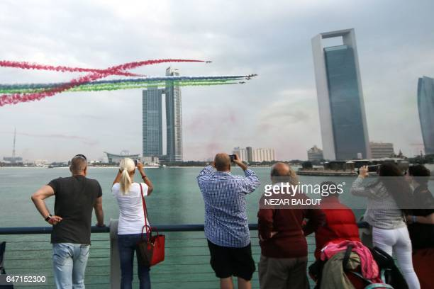 Spectators take pictures of Emirati planes performing in an airshow as part of the 'Union Fortress Live Military Demonstration' at the Abu Dhabi...