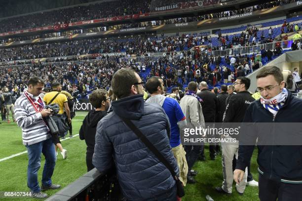 Spectators take refuge on the field as Besiktas' and Lyon's supporters fight in the tribunes before the Europa League football match Olympique...
