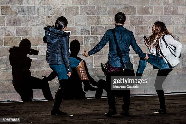 Spectators take 'selfies' as they cast shadows at the 'Placa del Rei' during the city's light festival 'Llum BCN' in Barcelona