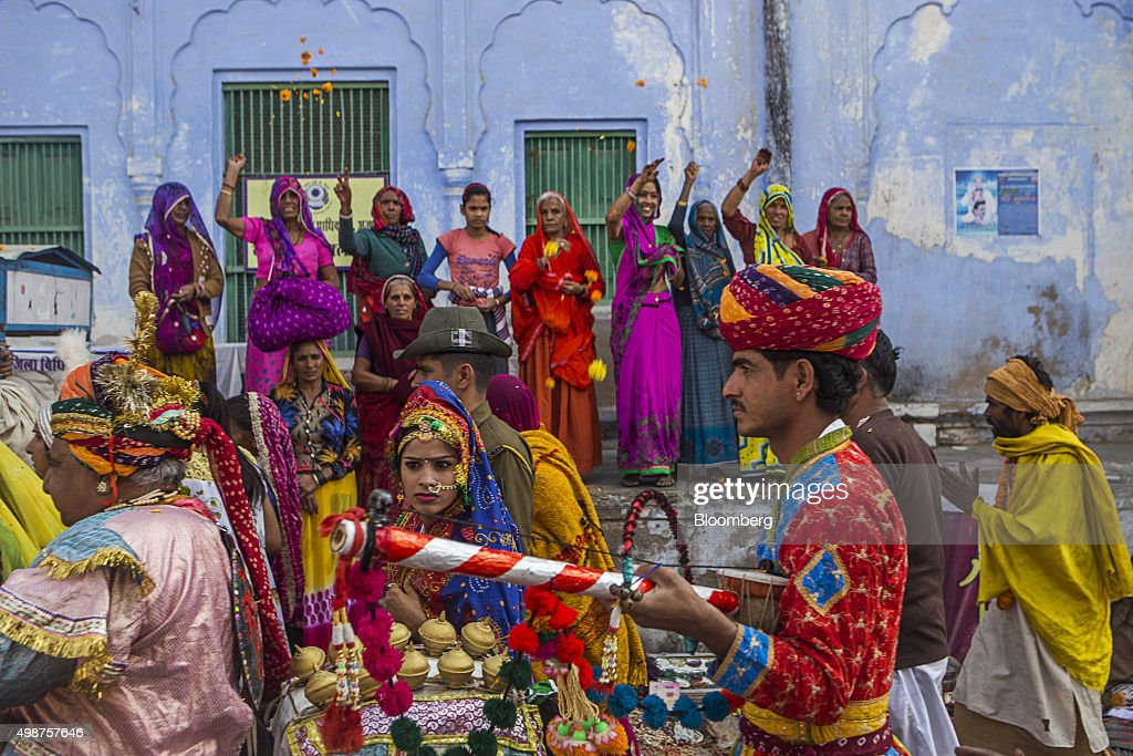 Spectators throw flowers at passing participants during a procession showcasing artists and children dressed as various Gods and Godesses through a...