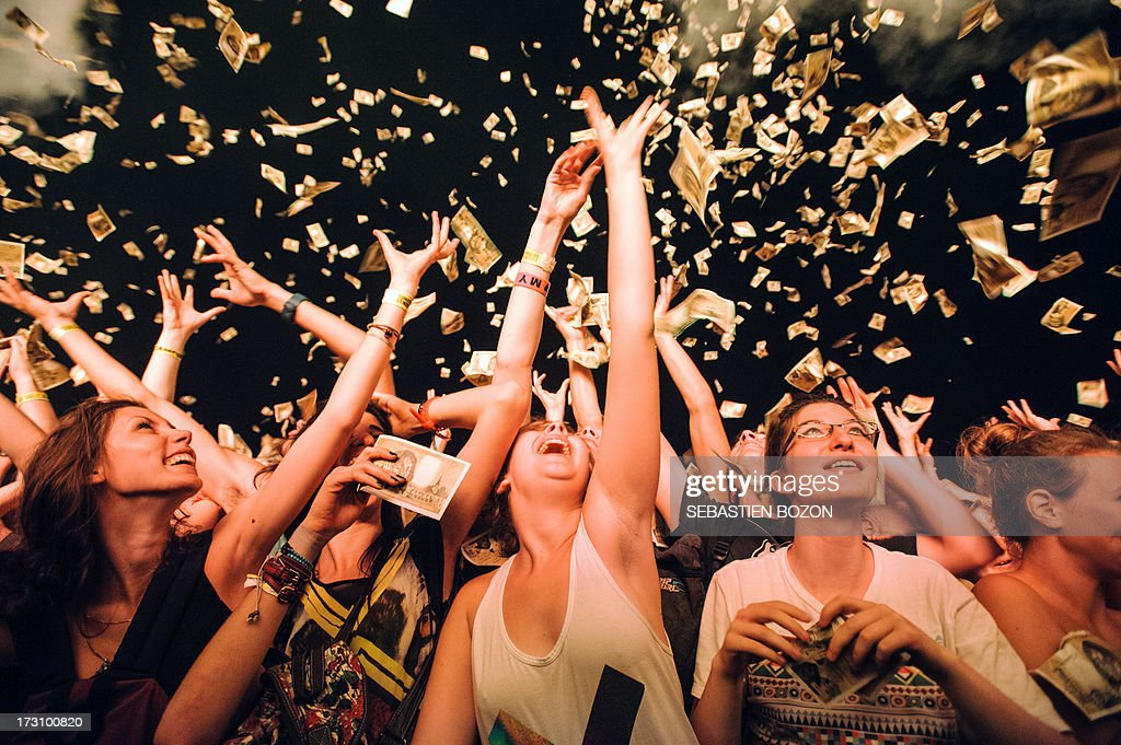 Spectators try to catch fake banknotes during the French band Phoenix' concert on July 6, 2013 on the third day of the Eurockeennes music festival, in the French eastern city of Belfort.