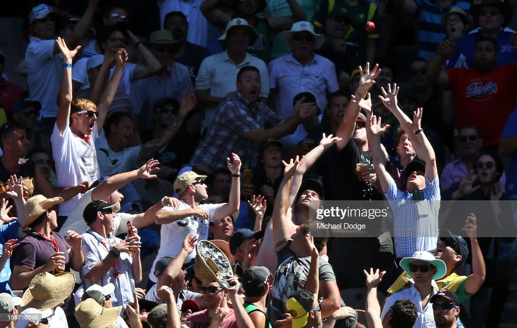 Spectators try to catch the ball hit by David Warner for six during day one of the Second Test match between Australia and Sri Lanka at Melbourne Cricket Ground on December 26, 2012 in Melbourne, Australia.