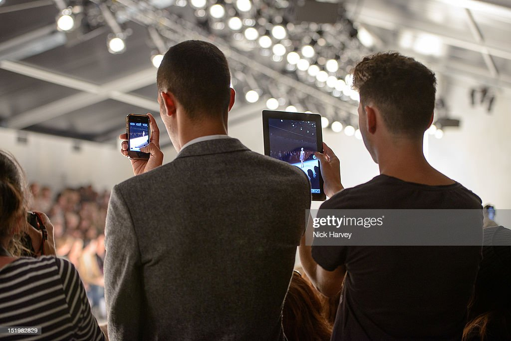 Spectators use an iPhone and iPad during the Maria Grachvogel catwalk show on day 1 of London Fashion Week Spring/Summer 2013, at the Courtyard Show Space on September 14, 2012 in London, England.