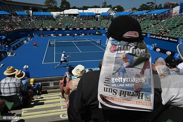 Spectators use newspapers to shield themselves from the sun as John Isner of the US plays a shot during his men's singles match against Austria's...