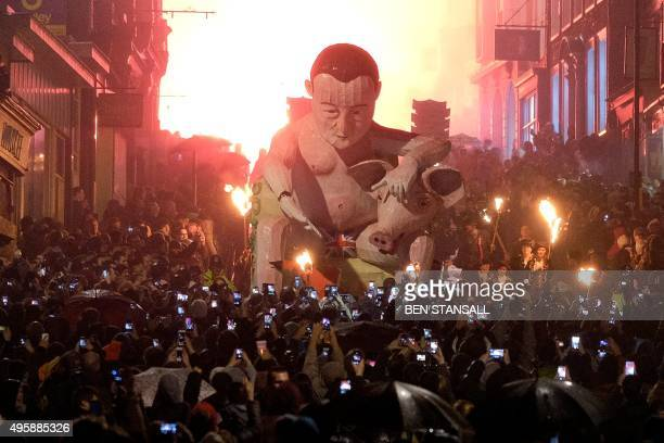 Spectators use smartphones to photograph an effigy depicting Britain's Prime Minister David Cameron as it is paraded through the streets of Lewes in...