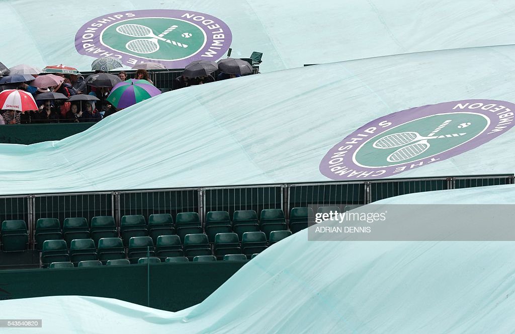 Spectators wait as rain delays the start of the third day of the 2016 Wimbledon Championships at The All England Lawn Tennis Club in Wimbledon, southwest London, on June 29, 2016. / AFP / ADRIAN