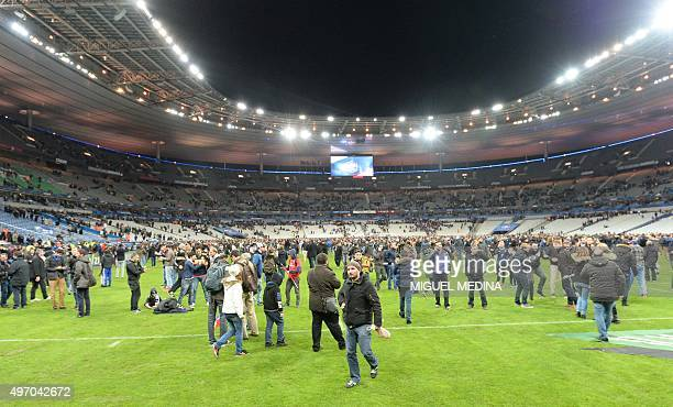 Spectators wait on the pitch of the Stade de France stadium following the friendly football match between France and Germany in SaintDenis north of...