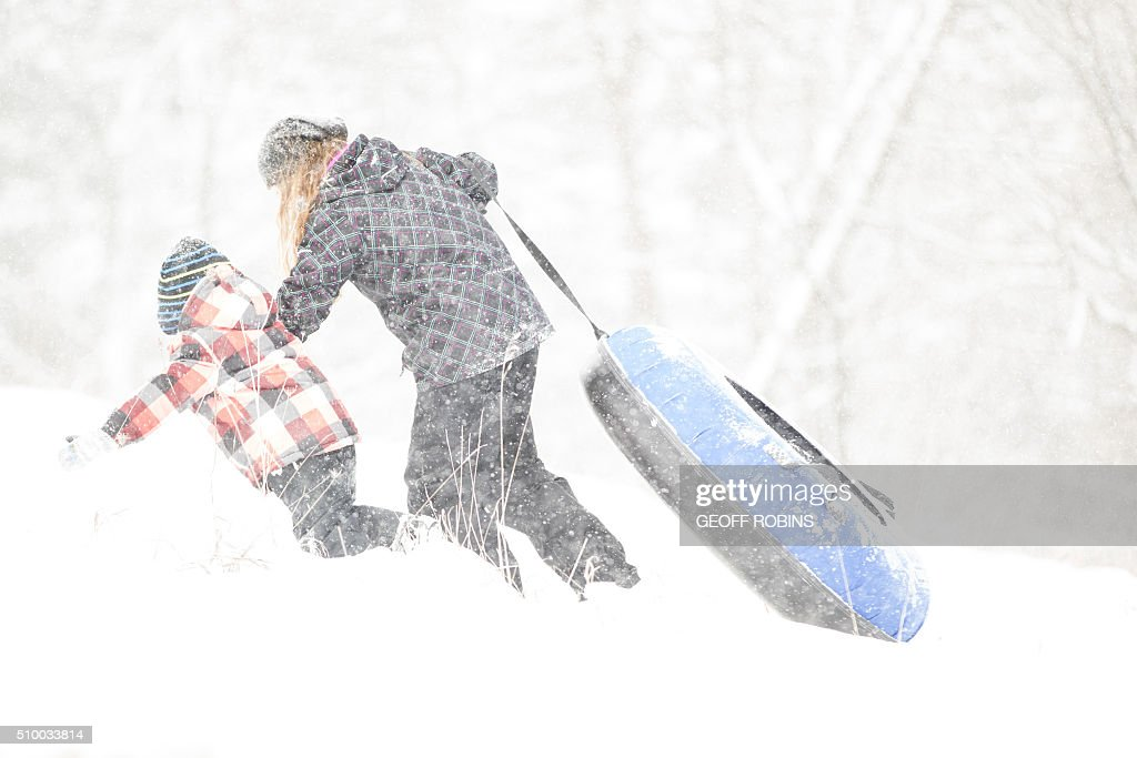 Spectators walk a tube back up the hill during a break in the competition at the World Tubing Championship in St. Thomas, Ontario, February 13, 2016. The inaugural event is a fundraiser for the Special Care Nursery at St. Thomas Elgin General Hospital attracted nearly 50 teams. / AFP / Geoff Robins