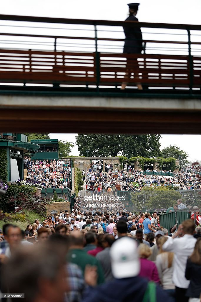 Spectators walk between courts on the fourth day of the 2016 Wimbledon Championships at The All England Lawn Tennis Club in Wimbledon, southwest London, on June 30, 2016. / AFP / ADRIAN