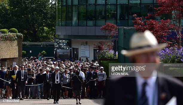Spectators walk in lead by security and stewards on day one of the 2015 Wimbledon Championships at The All England Tennis Club in Wimbledon southwest...