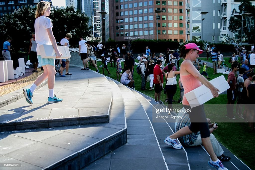 Spectators walk off with collapsed Dominoes during the Arts Centre Melbournes Dominoes arts project in Melbourne, Australia February 6, 2016. More than 7000 giant dominoes snaked through Melbourne city over 2km.