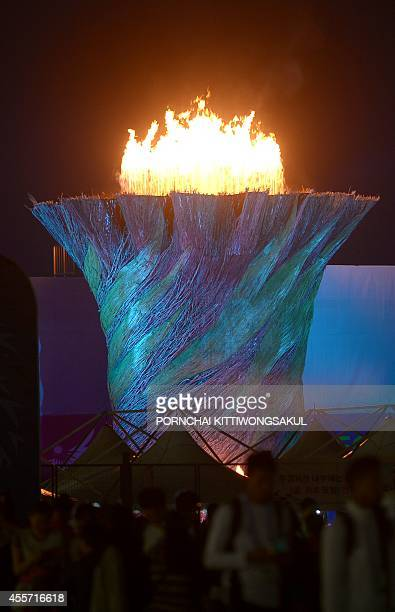 Spectators walk past the flame after it was lit during the opening ceremony of the 2014 Asian Games at the Incheon Asiad Main Stadium in Incheon on...