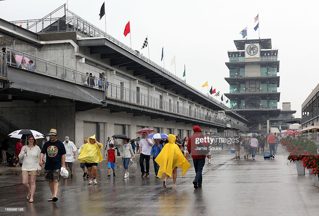 Spectators walk through Gasoline Alley during a rain delay prior to qualifying for the 2013 Indianapolis 500 at Indianapolis Motor Speedway on May 18, 2013 in Indianapolis, Indiana.