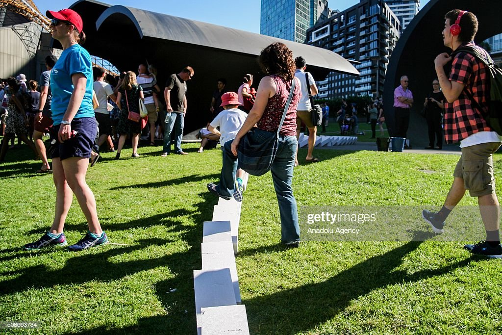 Spectators walkover collapsed dominoes during the Arts Centre Melbournes Dominoes arts project in Melbourne, Australia February 6, 2016. More than 7000 giant dominoes snaked through Melbourne city over 2km.