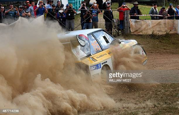 Spectators watch a competitor slide through a corner during the first day of the Rally of Australia World Rally Championship event near Macksville on...