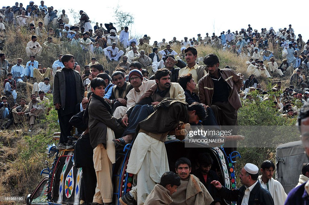 Spectators watch a dog fighting match in Chakwal, around 100 kilometers from Islamabad on February 17, 2013. Dog fighting and other forms of animal fighting are common in rural areas of Pakistan where some 70 percent of the population of 167 million reside. AFP PHOTO/Farooq NAEEM