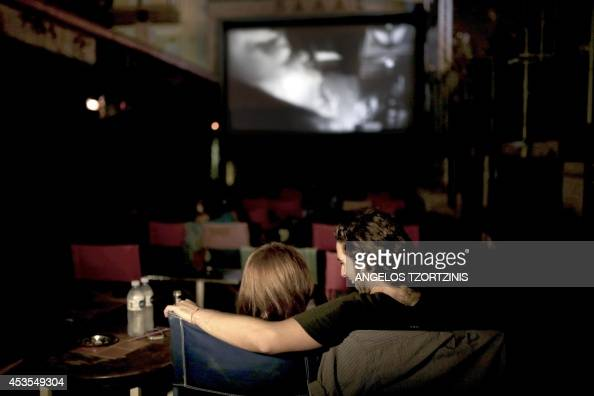 Spectators watch a film in the screening booth of 'Palas' one of Athens' oldest cinemas in the workingclass district of Pangratiin on July 30 2014 A...