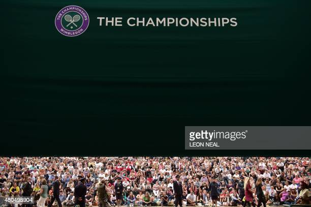 Spectators watch a giant screen showing the men's singles final match between Serbia's Novak Djokovic and Switzerland's Roger Federer as they sit on...