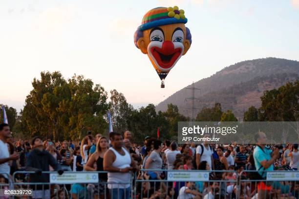 Spectators watch a hot air balloon from Slovakia in a shape of clown named 'Bruno' flying during the Gilboa Hot Air Balloon Festival near Kibbutz Ein...