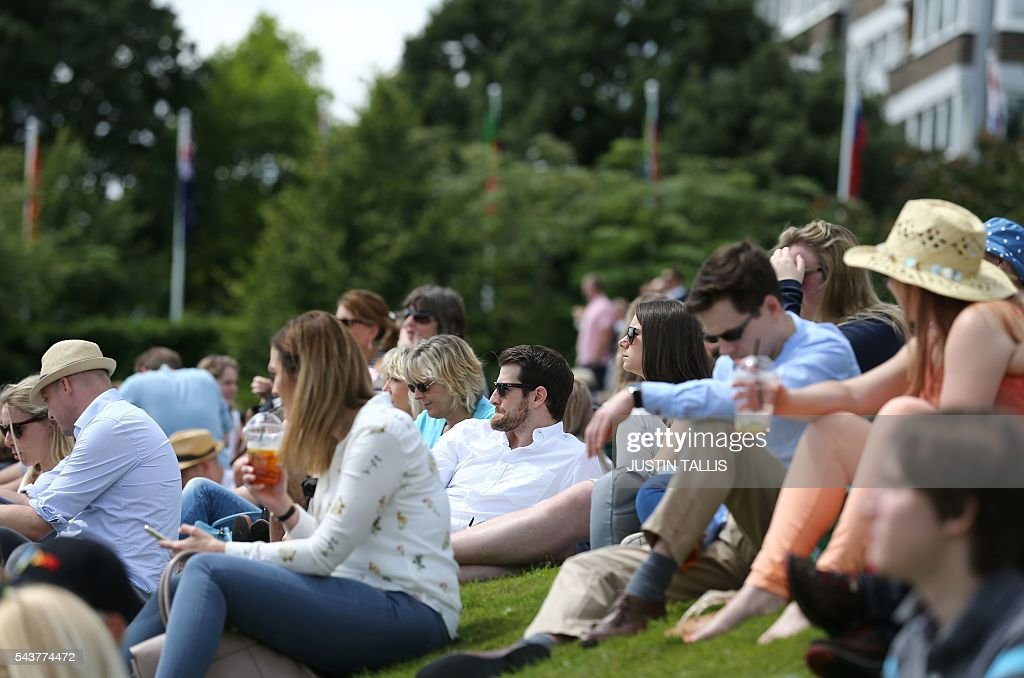 Spectators watch a large screen on Murray mount on the fourth day of the 2016 Wimbledon Championships at The All England Lawn Tennis Club in Wimbledon, southwest London, on June 30, 2016. / AFP / JUSTIN