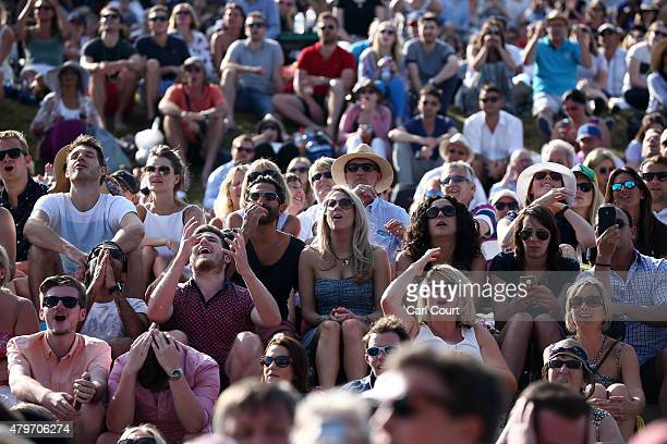 Spectators watch a large screen television from Murray Mound as Andy Murray of Great Britain plays Ivo Karlovic of Croatia in their Gentlemen's...