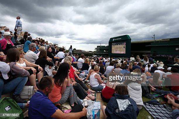 Spectators watch a large screen television from Murray Mound as Andy Murray of Great Britain plays against Vasek Pospisil of Canada in their...