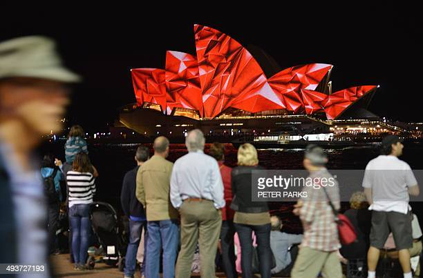 Spectators watch a light show called 'Vivid' performed on the Sydney Opera House in Sydney on May 25 2014 'Vivid' is a major outdoor cultural event...