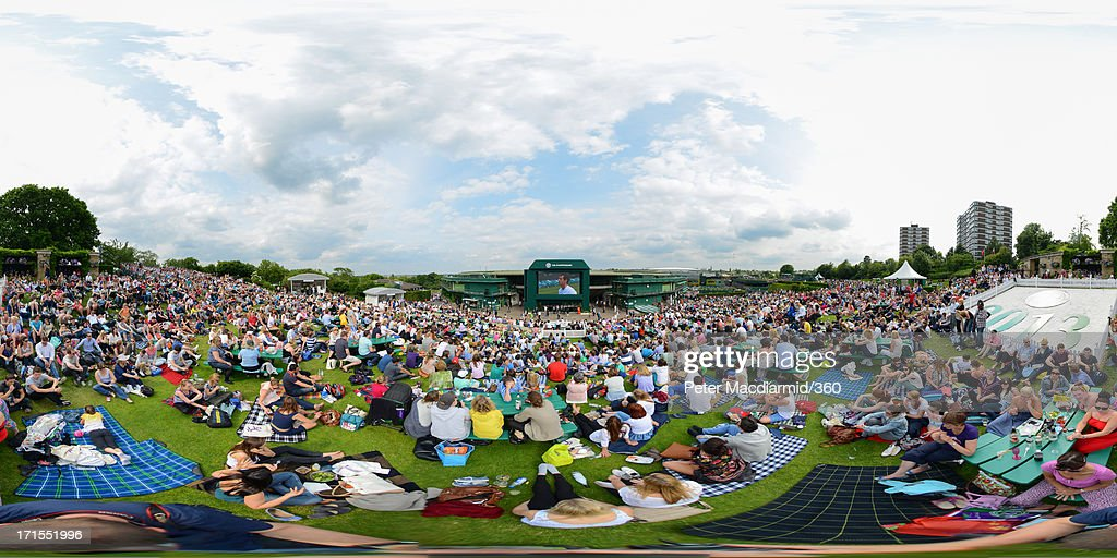Spectators watch a video screen showing Andy Murray of Great Britain's match against Lu Yen-Hsun of Taipei on day three of the Wimbledon Lawn Tennis Championships at the All England Lawn Tennis and Croquet Club on June 26, 2013 in London, England.