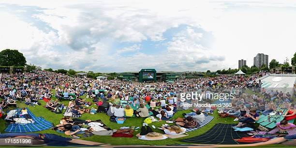 Spectators watch a video screen showing Andy Murray of Great Britain's match against Lu YenHsun of Taipei on day three of the Wimbledon Lawn Tennis...