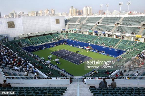 Spectators watch action on the court at the just completed Beijing Tennis Centre 22 September 2004 during a second round match between China's Zheng...