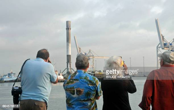 Spectators watch and take pictures as Space X's Falcon 9 first stage arrives in Port Canaveral Florida on April 4 2017 abaord its landing platform...