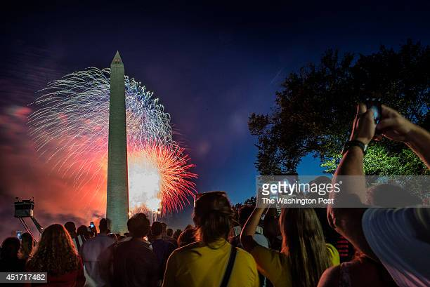 Spectators watch and take snapshots of the annual Independence Day fireworks display at the Washington Monument on July 2014 in Washington DC