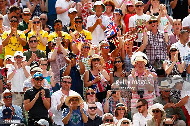Spectators watch Andy Murray of Great Britain in his Gentlemen's Singles Fourth Round match against Ivo Karlovic of Croatia during day seven of the...