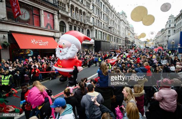 Spectators watch as a giant inflatable Santa is paraded during the Hamleys Christmas Toy Parade on Regent Street in London on November 28 2015 AFP...