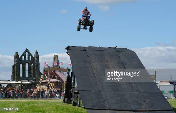 Spectators watch as a motorcycle stunt performer jumps between trucks during the Whitby Traction Engine Rally on August 4 2017 in Whitby England...