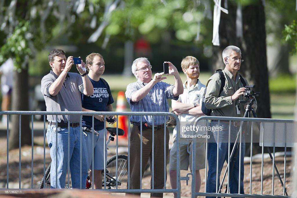 Spectators watch as crews from the Asplundh tree service cut down an oak tree on April 23, 2013 at Toomer's Corner in Auburn, Alabama. Auburn University decided to remove the dying oaks after they were poisoned by a rival fan shortly after the 2010 Iron Bowl.