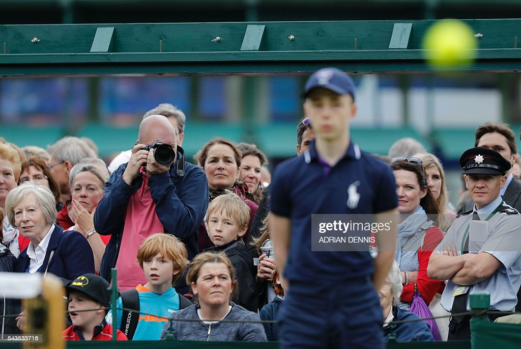 Spectators watch as Czech Republic's Tomas Berdych warms up with Croatia's Ivan Dodig during a men's singles first round match on the third day of the 2016 Wimbledon Championships at The All England Lawn Tennis Club in Wimbledon, southwest London, on June 29, 2016. / AFP / ADRIAN