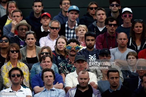 Spectators watch as France's Richard Gasquet plays against Switzerland's Stan Wawrinka during their men's quarterfinals match on day nine of the 2015...