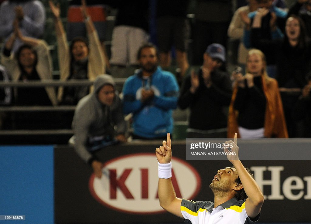 Spectators watch as Marcos Baghdatis of Cyprus celebrates after victory in his men's singles match against Albert Ramos of Spain on the first day of the Australian Open tennis tournament in Melbour...